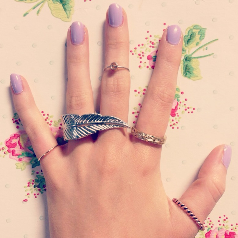 A picture of a hand wearing rings and Essie lilacism nail polish