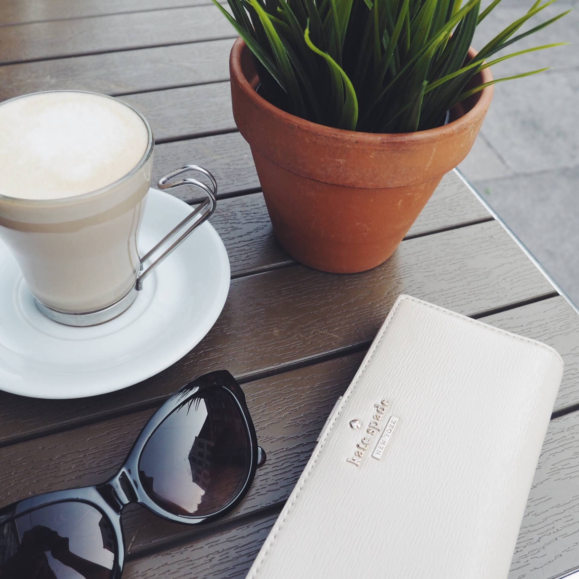 A picture of Latte, sunglasses and Kate Spade wallet